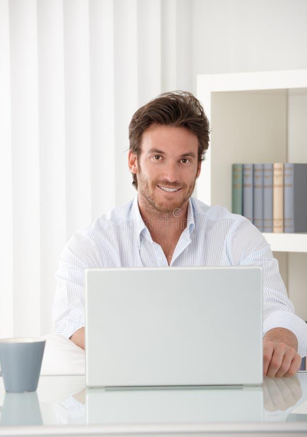 Lächelnder Geschäftsmann mit Laptop lizenzfreies stockfoto