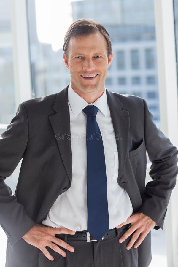 Lächelnder Geschäftsmann mit seinen Händen auf Hüften lizenzfreie stockbilder