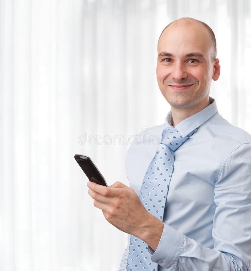Lächelnder Geschäftsmann mit Telefon lizenzfreies stockfoto