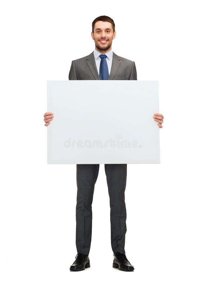 Lächelnder Geschäftsmann mit weißem leerem Brett lizenzfreie stockfotos