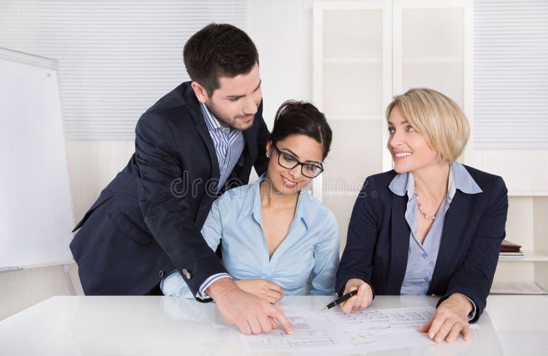 Lächelnder Geschäftsmann unter Verwendung des Laptop cmputer am Schreibtisch und Unterhaltung mit einer Frau Drei Leute, die am T stockfoto