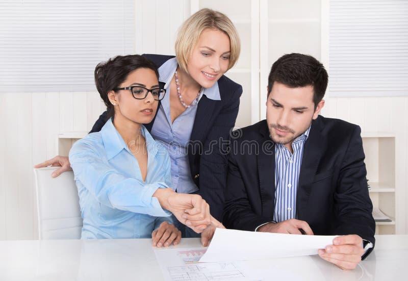 Lächelnder Geschäftsmann unter Verwendung des Laptop cmputer am Schreibtisch und Unterhaltung mit einer Frau Drei Leute, die am T stockbild