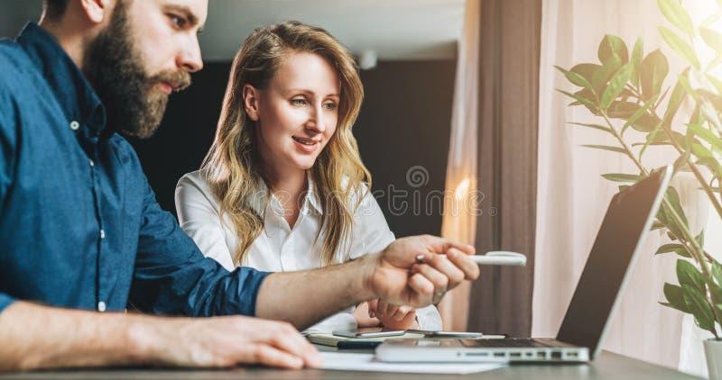 Lächelnder Geschäftsmann unter Verwendung des Laptop cmputer am Schreibtisch und Unterhaltung mit einer Frau teamwork Geschäftsfr lizenzfreie stockbilder