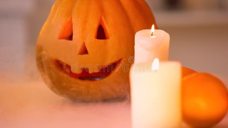 Lächelnder geschnitzter Halloween-Kürbis mit dem furchtsamen Gesicht belichtet durch das Brennen von Kerzen stockbild