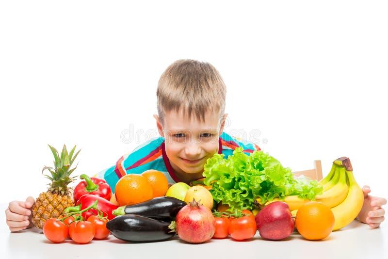 Lächelnder gesunder Junge mit einem Bündel saftigem reifem Gemüse und Früchten auf einem Weiß lizenzfreies stockfoto