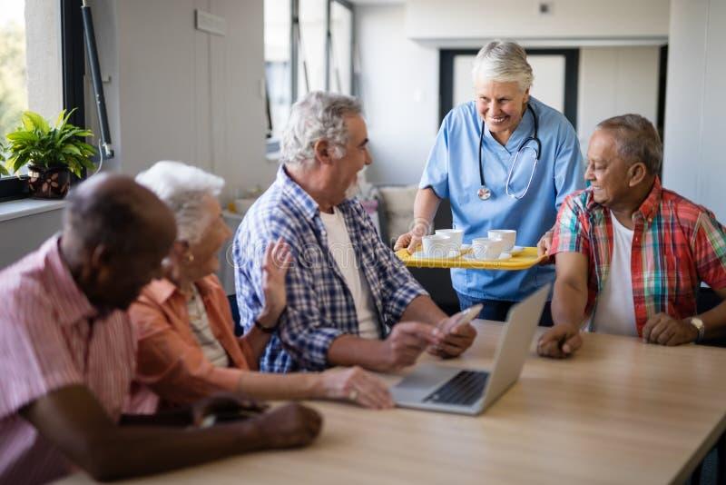 Lächelnder Gesundheitswesenarbeitskraft-Umhüllungskaffee zu den älteren Leuten stockfotografie
