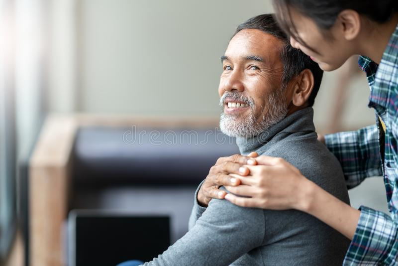 Lächelnder glücklicher älterer asiatischer Vater mit ` s Tochter des stilvollen kurzen Bartes rührender Hand auf dem Schulterscha lizenzfreie stockfotos