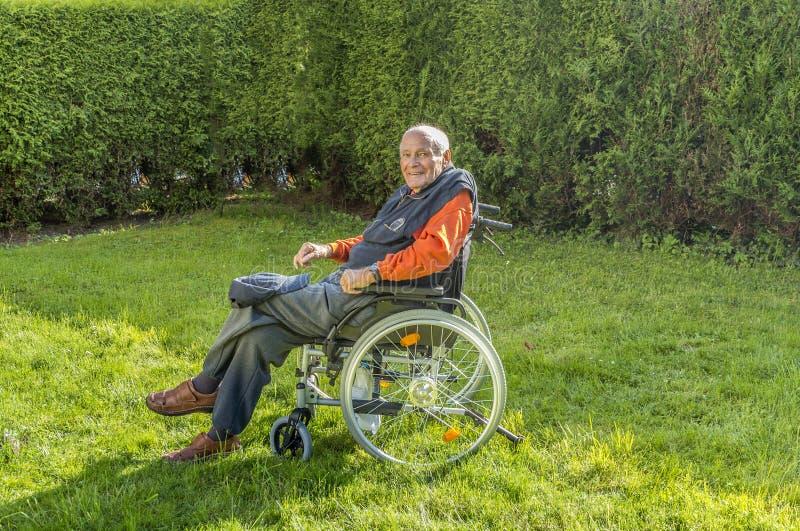 Lächelnder glücklicher älterer Mann, der in seinem Garten sitzt lizenzfreie stockfotos