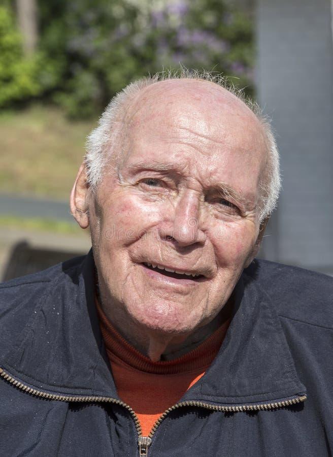 Lächelnder glücklicher älterer Mann, der in seinem Garten sitzt lizenzfreies stockfoto