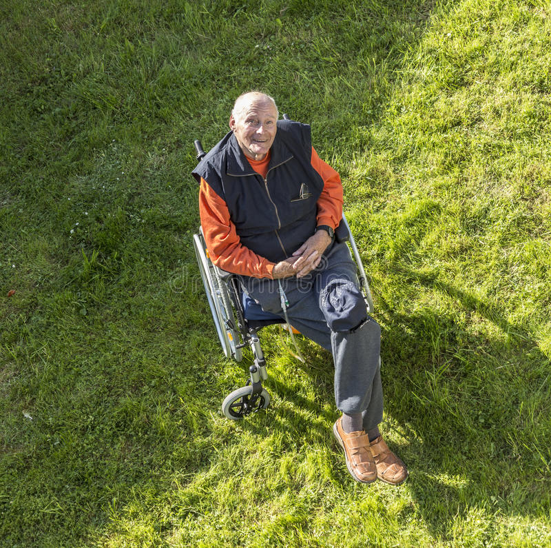 Lächelnder glücklicher älterer Mann, der in seinem Garten sitzt stockfoto