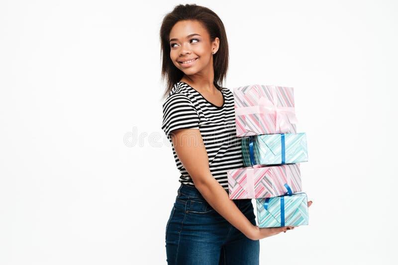 Lächelnder glücklicher afrikanischer Frauenholdingstapel Präsentkartons lizenzfreie stockfotos
