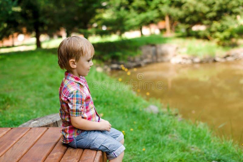 Lächelnder glücklicher Junge, der auf Bank nahe See sitzt Sommerzeit weeken stockfoto