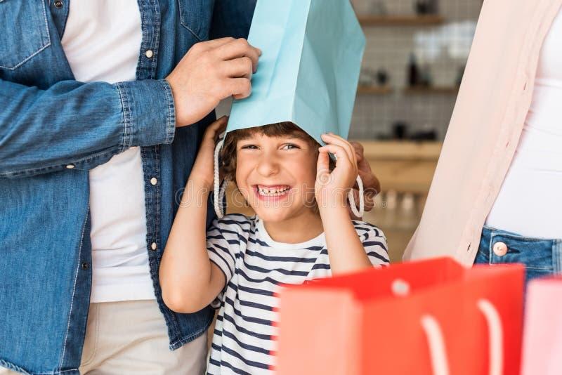 lächelnder glücklicher Junge mit Einkaufstasche auf Kopf stockfotografie