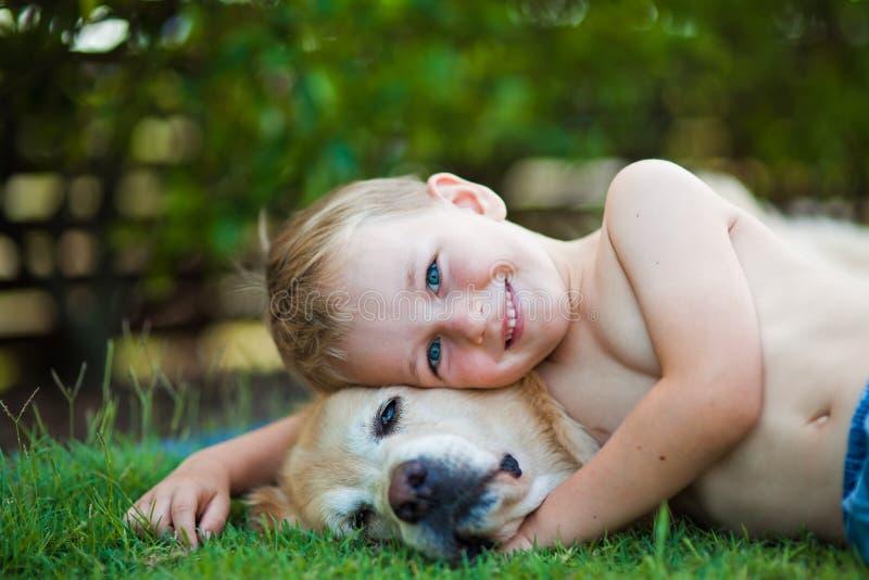 Lächelnder glücklicher Junge und sein golden retriever im Gras stockbild