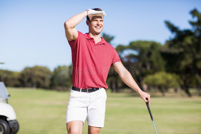 Lächelnder Golfspieler, der Augen abschirmt lizenzfreie stockfotografie