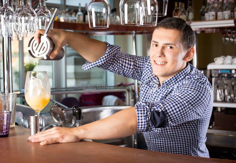 Lächelnder hübscher Barmixer, der ein Getränk in das Glas aus gießt stockfoto