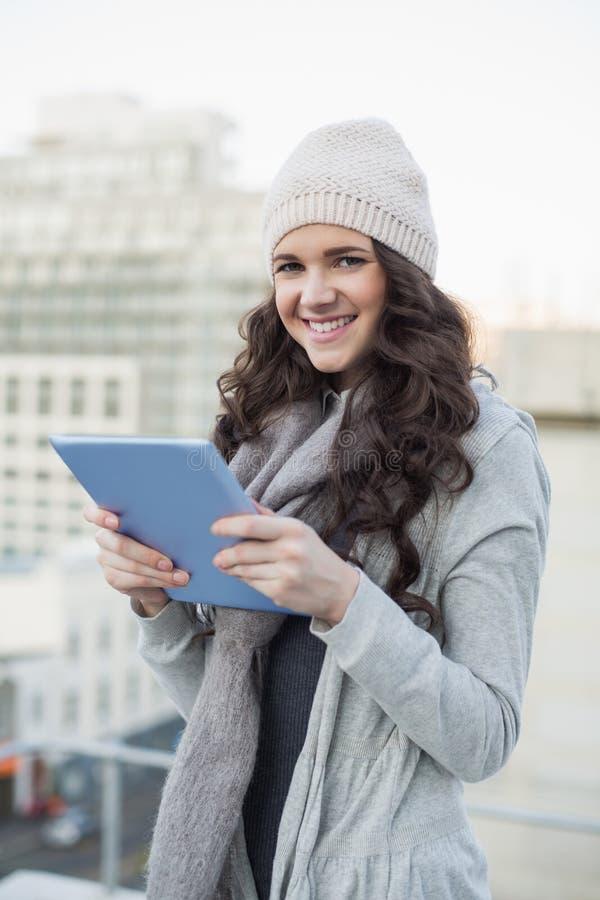 Lächelnder hübscher Brunette, der ihren Tabletten-PC hält stockfotografie
