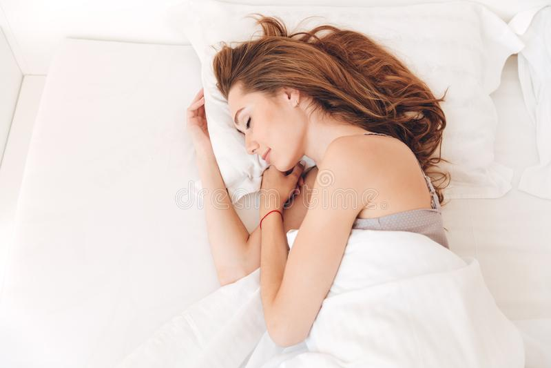 Lächelnder hübscher Damenschlaf im Bett zuhause Augen geschlossen stockfotos
