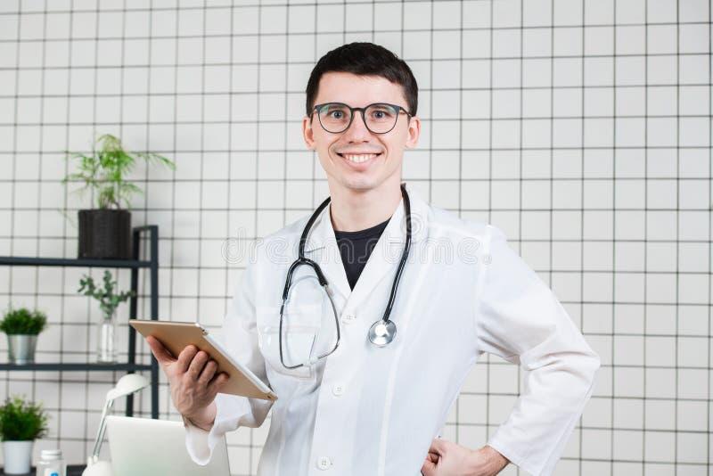 Lächelnder hübscher junger männlicher Doktor unter Verwendung des Tablet-Computers Technologien im Medizinkonzept stockfotos