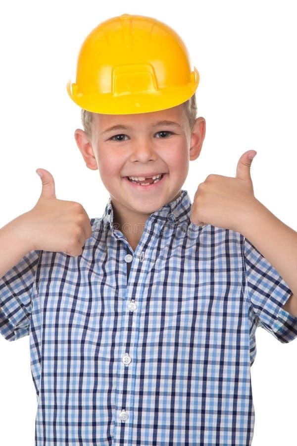 Lächelnder hübscher kaukasischer jugendlich Junge in einem gelben Schutzhelm Das glückliche Kind, das Daumen herstellt, up Geste  stockfotografie