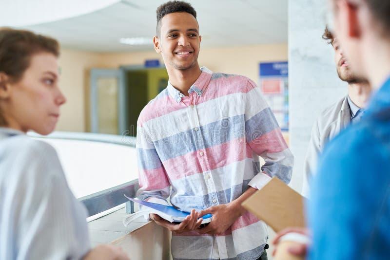 Lächelnder hübscher Student, der mit groupmates spricht lizenzfreie stockbilder