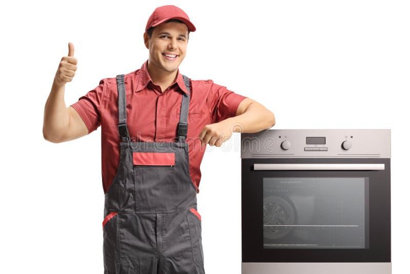 Lächelnder Heimwerker in einer einheitlichen Stellung nahe bei einem elektrischen Ofen-ANG, das Daumen aufgibt stockbild