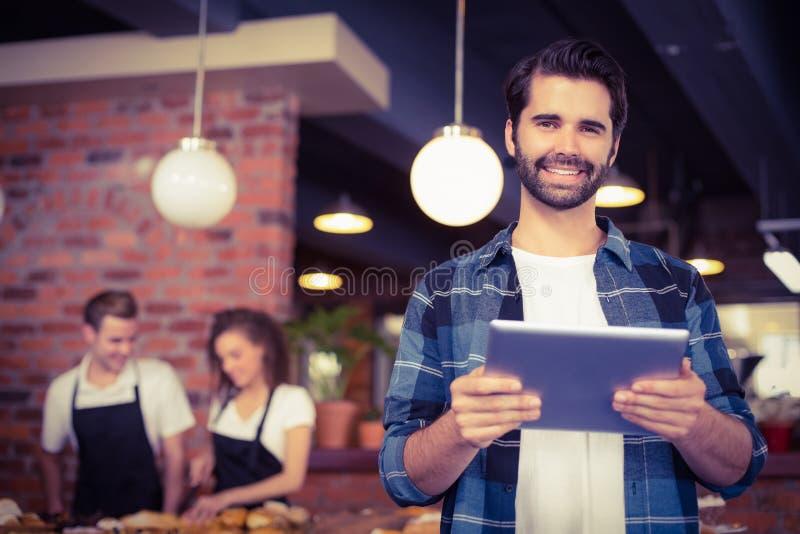 Lächelnder Hippie, der Tablette vor Arbeits-barista verwendet lizenzfreies stockfoto