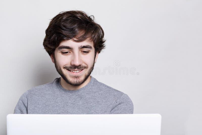 Lächelnder Hippie mit dem modischen Bart, der zu Hause mit seinem Notizbuch ist glücklich arbeitet, etwas Videos über weißem back lizenzfreie stockfotografie