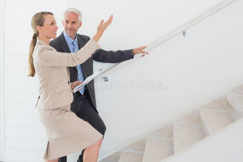 Lächelnder Immobilienmakler, der dem möglichen Käufer Treppe zeigt stockfotos