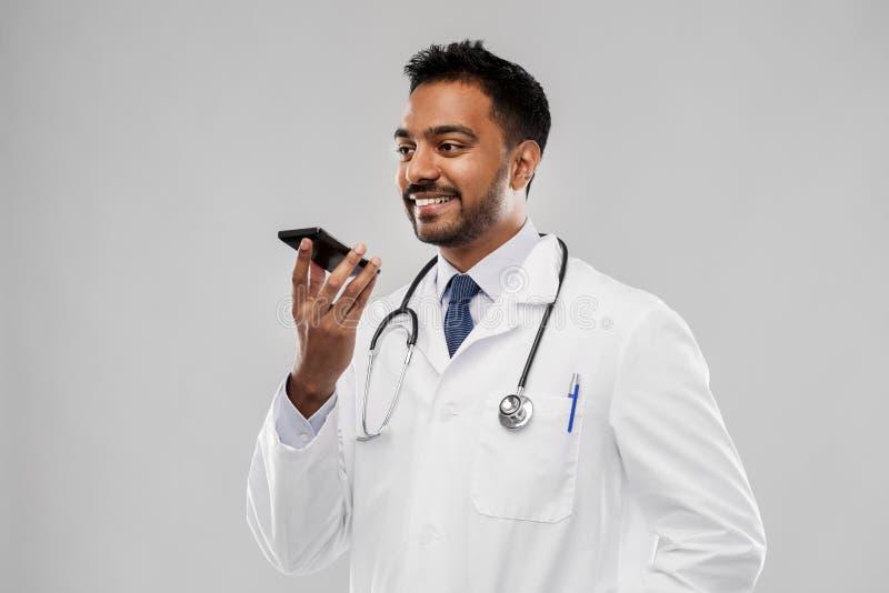 Lächelnder indischer männlicher Doktor, der um Smartphone ersucht stockfotos