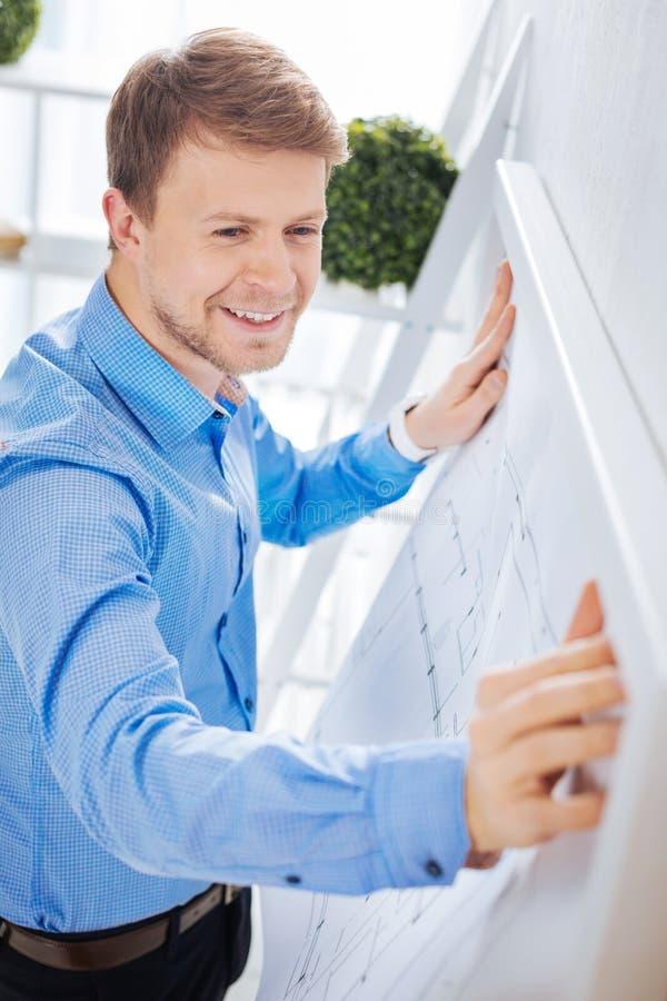 Lächelnder Ingenieur, der seine große Zeichnung auf der Wand hängt lizenzfreies stockbild
