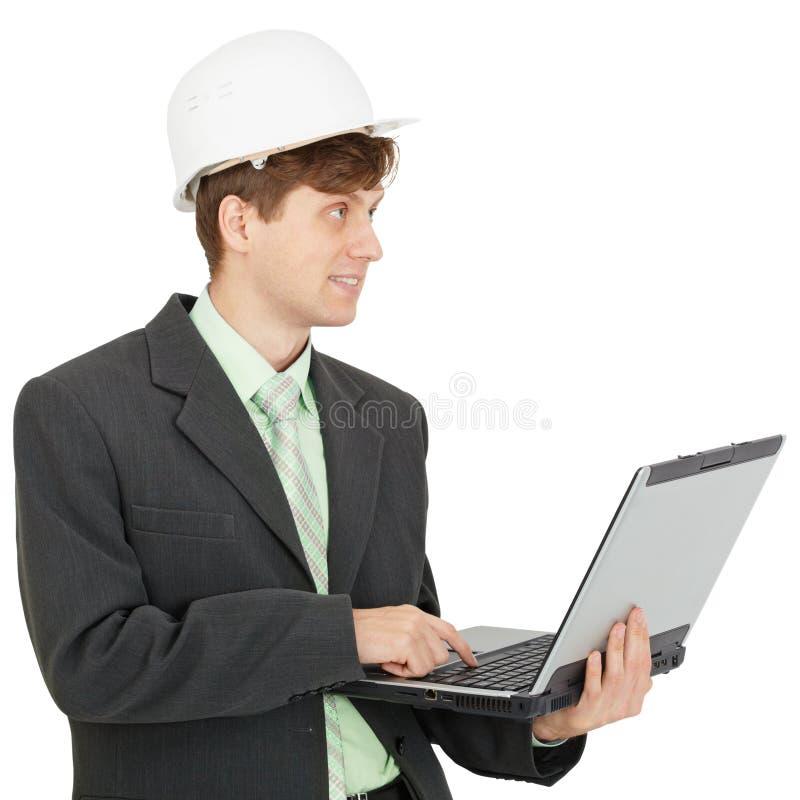Lächelnder Ingenieur im Sturzhelm mit Laptop in den Händen lizenzfreie stockfotografie