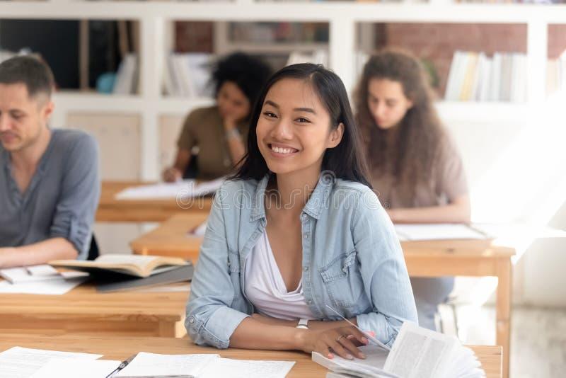 Lächelnder intelligenter asiatischer Student, der die Kamera sitzt am Schreibtisch betrachtet stockbild