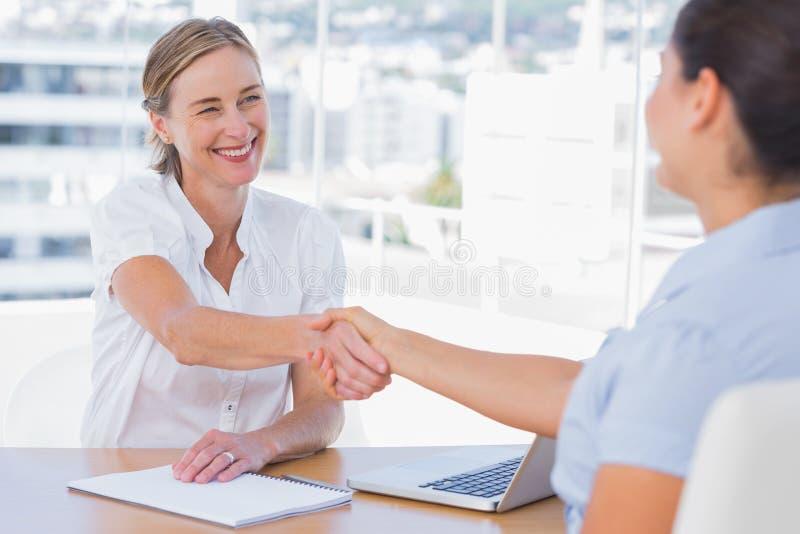 Lächelnder Interviewer, der Hand eines Bewerbers rüttelt lizenzfreies stockbild