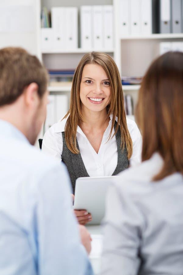 Lächelnder Investitionsmakler, der mit Kunden spricht stockbild