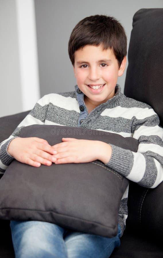 Lächelnder Jugendlicher auf dem Sofa zu Hause lizenzfreie stockfotos