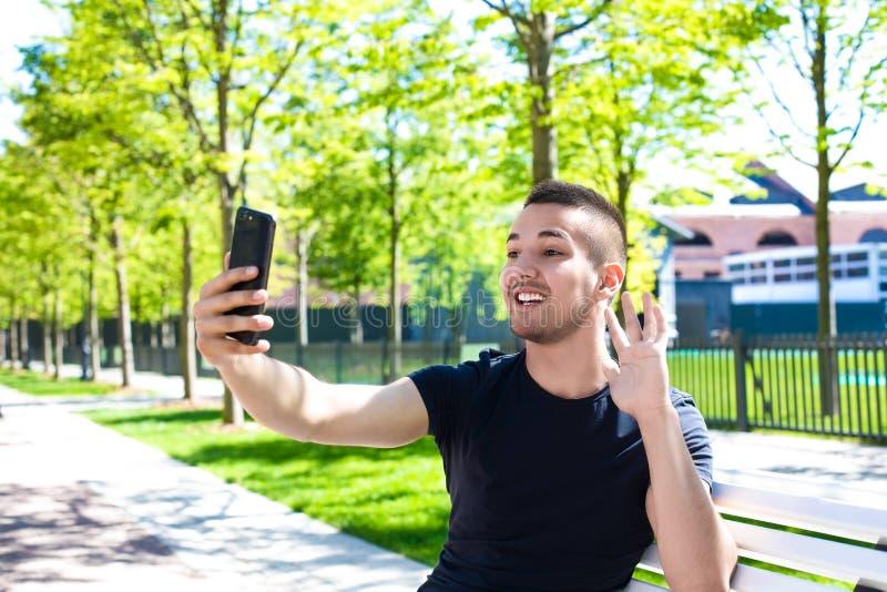 Lächelnder Jugendlicher, der über Handykamera während der Erholung spricht stockbilder