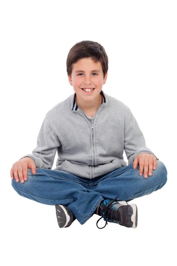 Lächelnder jugendlicher Junge, der auf dem Boden sitzt stockfotografie