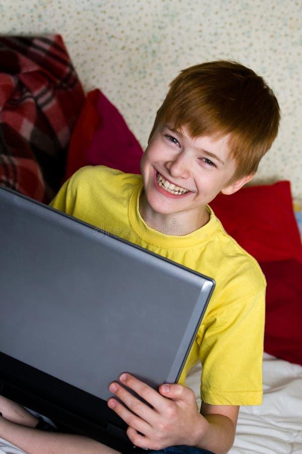 Lächelnder Jugendlicher mit einem Laptop stockfotos