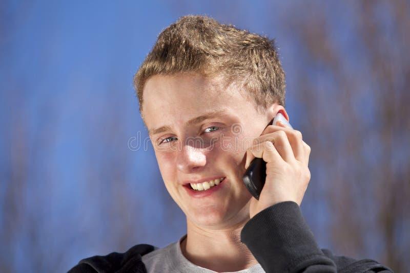 Lächelnder Jugendlicher mit Handy stockfotografie