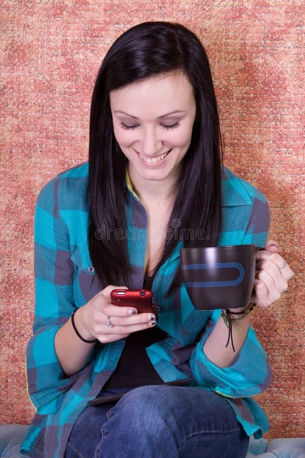 Lächelnder Jugendlicher trinkender Kaffee und Texting stockfotografie