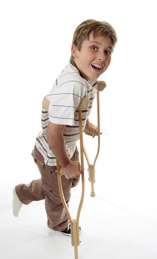Lächelnder Junge auf Krückeen lizenzfreie stockfotografie