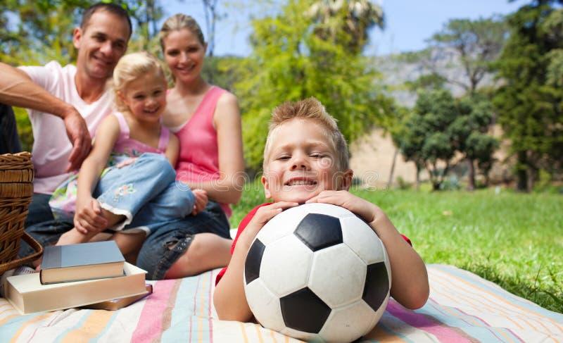 Lächelnder Junge, der eine Fußballkugel anhält stockbilder