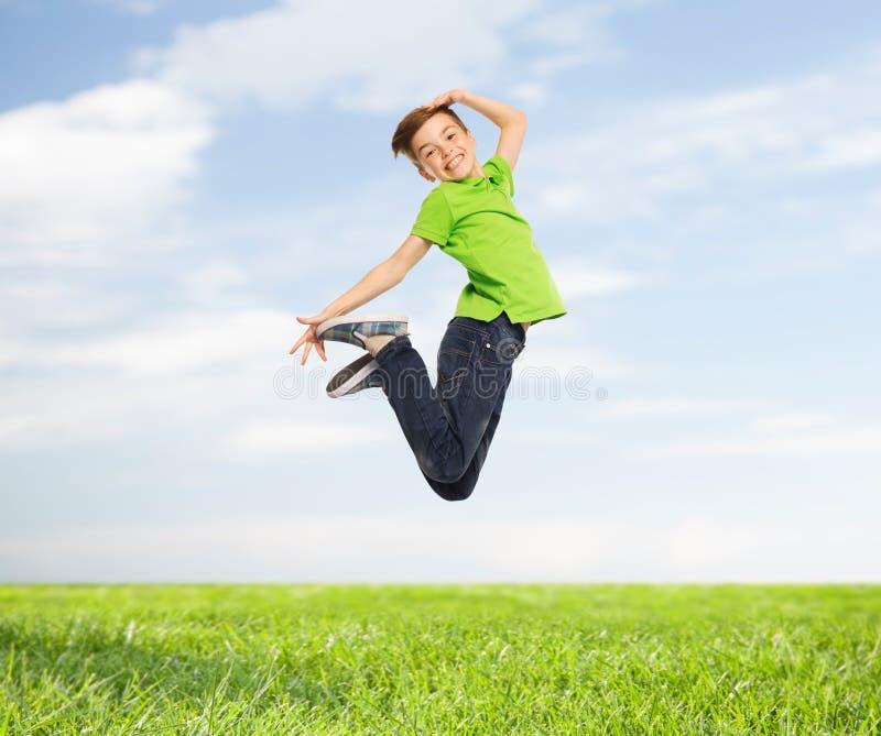 Lächelnder Junge, der in einer Luft springt lizenzfreie stockfotografie