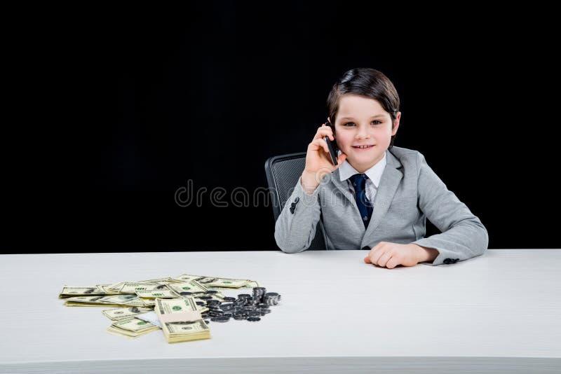 Lächelnder Junge, der Geschäftsmann spielt und auf Smartphone auf Schwarzem spricht stockbild