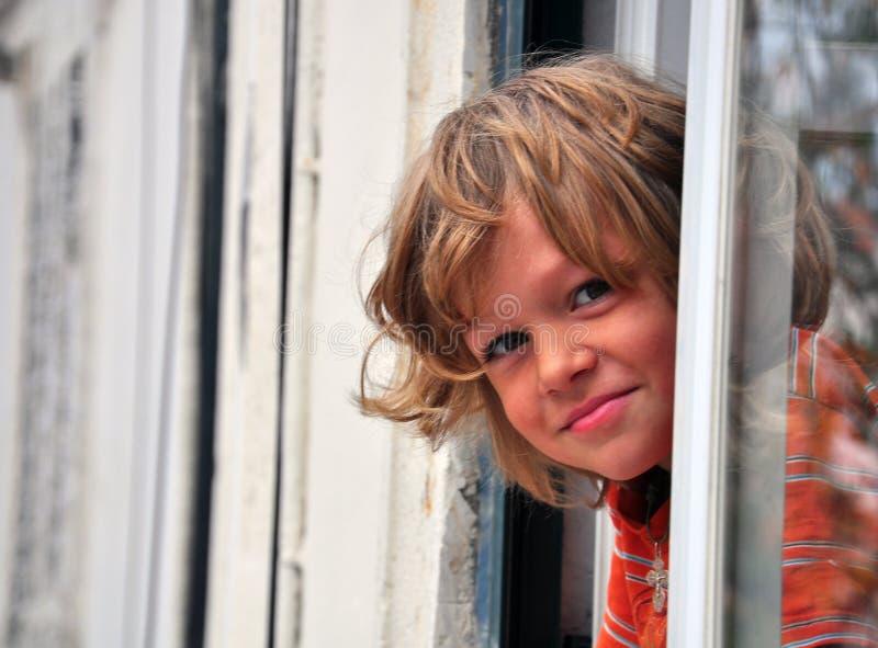 Lächelnder Junge, Der Heraus Schaut Stockfotografie