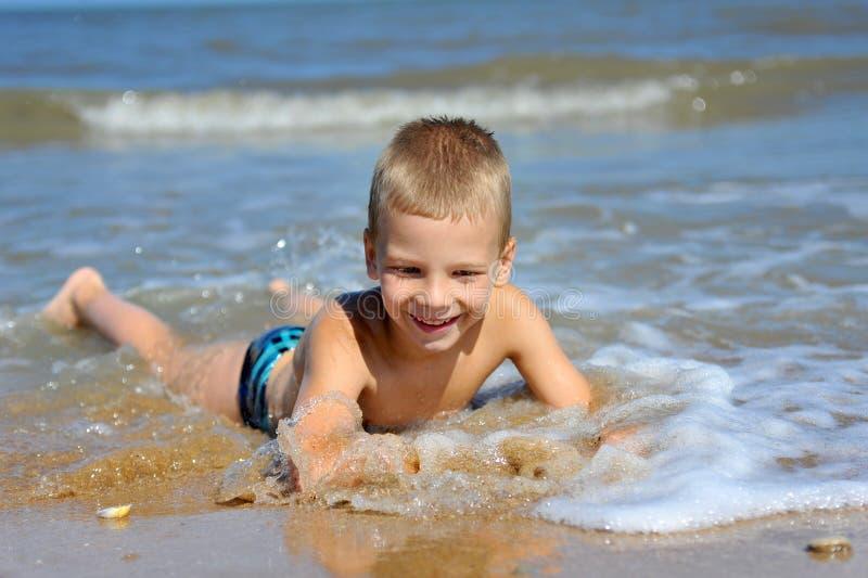 Lächelnder Junge, der im Wasser am Strand liegt stockbilder