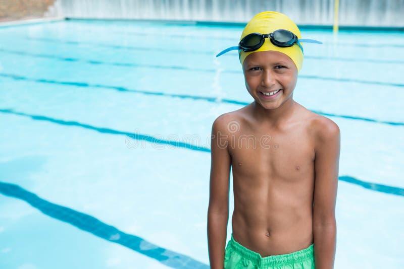 Lächelnder Junge, der nahen Poolside steht lizenzfreie stockbilder