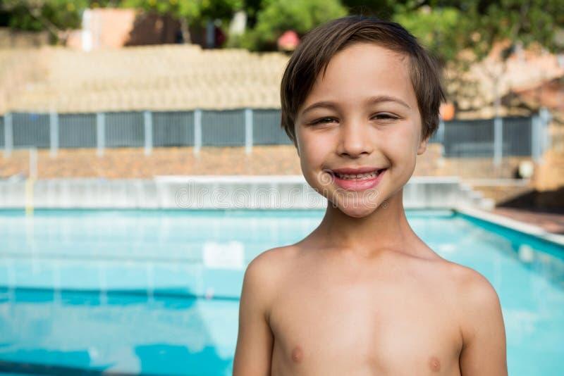 Lächelnder Junge, der nahen Poolside steht stockbild