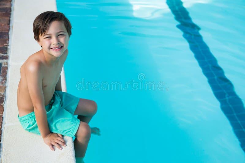 Lächelnder Junge, der am Poolside sitzt stockfoto